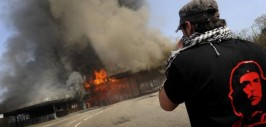 An anti-NATO protestor takes a photograph of the smashed and burning former border police station between Strasbourg and Kehl during a rally against the NATO summit in Strasbourg